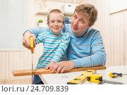 Купить «father teaches his son to cut the wooden plank saw», фото № 24709839, снято 21 февраля 2016 г. (c) Константин Лабунский / Фотобанк Лори