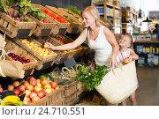 Купить «female customer with daughter choosing fruits», фото № 24710551, снято 25 мая 2020 г. (c) Яков Филимонов / Фотобанк Лори
