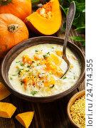 Купить «Сырный суп с тыквой и пшеном на деревянном столе», фото № 24714355, снято 14 декабря 2016 г. (c) Надежда Мишкова / Фотобанк Лори