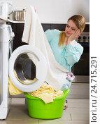Купить «Upset young woman cannot remove stains off bed linen», фото № 24715291, снято 21 января 2020 г. (c) Яков Филимонов / Фотобанк Лори