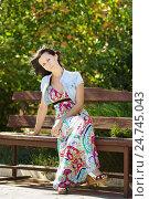 Купить «Красивая молодая женщина славянской внешности сидит на старой скамейке в парке солнечным ветреным днем», фото № 24745043, снято 26 августа 2015 г. (c) Наталья Гармашева / Фотобанк Лори