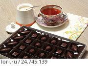 Купить «Шоколадные конфеты в коробке, сахарница и чашка чая на столе», эксклюзивное фото № 24745139, снято 21 декабря 2016 г. (c) Яна Королёва / Фотобанк Лори