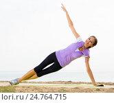 Купить «Woman practising yoga poses standing on beach», фото № 24764715, снято 26 мая 2019 г. (c) Яков Филимонов / Фотобанк Лори