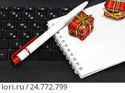 Купить «Новогодние подарки, ручка и блокнот для записей на клавиатуре ноутбука», фото № 24772799, снято 23 декабря 2016 г. (c) Наталья Осипова / Фотобанк Лори