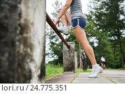 Купить «Молодая девушка делает упражнения на растяжку перед тренировкой на открытом воздухе», фото № 24775351, снято 6 декабря 2016 г. (c) Галаганов Дмитрий Александрович / Фотобанк Лори