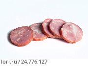Нарезанные ломтики колбасы на светлом фоне. Стоковое фото, фотограф Igor Sirbu / Фотобанк Лори