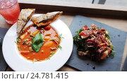 Купить «gazpacho soup, salads and drink at restaurant», видеоролик № 24781415, снято 29 сентября 2016 г. (c) Syda Productions / Фотобанк Лори