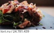 Купить «prosciutto ham salad on stone plate at restaurant», видеоролик № 24781439, снято 29 сентября 2016 г. (c) Syda Productions / Фотобанк Лори