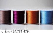 Купить «row of colorful thread spools on table», видеоролик № 24781479, снято 3 октября 2016 г. (c) Syda Productions / Фотобанк Лори