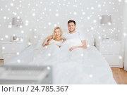 Купить «happy couple lying in bed at home and watching tv», фото № 24785367, снято 25 февраля 2016 г. (c) Syda Productions / Фотобанк Лори