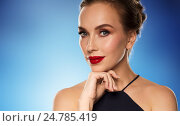 Купить «beautiful woman in black over blue background», фото № 24785419, снято 14 апреля 2016 г. (c) Syda Productions / Фотобанк Лори