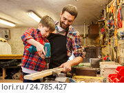Купить «father and son with drill working at workshop», фото № 24785427, снято 14 мая 2016 г. (c) Syda Productions / Фотобанк Лори