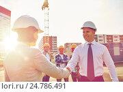 Купить «builders making handshake on construction site», фото № 24786491, снято 21 сентября 2014 г. (c) Syda Productions / Фотобанк Лори