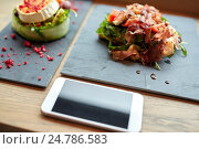 Купить «goat cheese and ham salads with smartphone at cafe», фото № 24786583, снято 22 сентября 2016 г. (c) Syda Productions / Фотобанк Лори