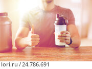 Купить «man with protein shake bottle showing thumbs up», фото № 24786691, снято 14 мая 2015 г. (c) Syda Productions / Фотобанк Лори