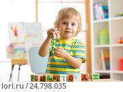 Купить «Little preschooler kid boy playing with toy cubes and memorizing letters. Early education and preschool concept», фото № 24798035, снято 17 декабря 2016 г. (c) Оксана Кузьмина / Фотобанк Лори