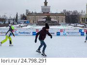 Молодые люди катаются на коньках на открытом катке на ВДНХ на фоне выставочного павильона Украина в городе Москве, Россия (2016 год). Редакционное фото, фотограф Николай Винокуров / Фотобанк Лори