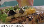 Купить «Close up view of meal on the plate, that woman waters lemon juice. potatoes, salad and chicken barbecue», видеоролик № 24798655, снято 27 октября 2016 г. (c) Данил Руденко / Фотобанк Лори