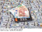Купить «Folded stack of russian roubles, euro banknotes and calculator on dollars background», фото № 24814607, снято 4 января 2017 г. (c) FotograFF / Фотобанк Лори