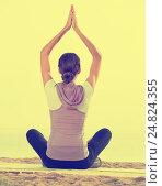 Купить «Young woman practise yoga cross-legged», фото № 24824355, снято 22 октября 2018 г. (c) Яков Филимонов / Фотобанк Лори