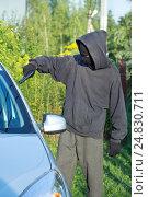 Купить «Мужчина в маске угрожает пистолетом водителю автомобиля», фото № 24830711, снято 11 августа 2016 г. (c) Сергей Лаврентьев / Фотобанк Лори