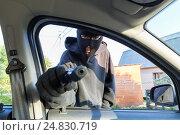 Купить «Человек в маске угрожает пистолетом водителю автомобиля», фото № 24830719, снято 11 августа 2016 г. (c) Сергей Лаврентьев / Фотобанк Лори