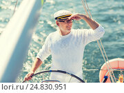senior man at helm on boat or yacht sailing in sea. Стоковое фото, фотограф Syda Productions / Фотобанк Лори