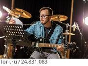 Купить «man playing guitar at studio rehearsal», фото № 24831083, снято 18 августа 2016 г. (c) Syda Productions / Фотобанк Лори