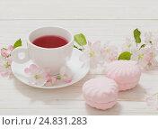 Купить «Red tea with flowers on white wooden background», фото № 24831283, снято 13 мая 2016 г. (c) Майя Крученкова / Фотобанк Лори