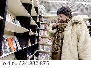 Пожилая женщина задумчиво выбирает книгу в книжном магазине, фото № 24832875, снято 6 января 2017 г. (c) Эдуард Паравян / Фотобанк Лори