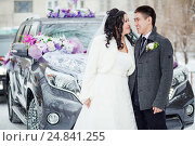 Купить «Winter wedding, the happy couple before the decorated car on a snowy street. Bride and groom look at each other.», фото № 24841255, снято 20 февраля 2016 г. (c) Евгений Майнагашев / Фотобанк Лори