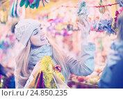Купить «Young positive woman at fair near counter with Christmas gifts», фото № 24850235, снято 27 января 2020 г. (c) Яков Филимонов / Фотобанк Лори
