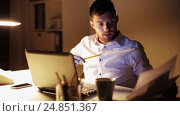 Купить «man with laptop and papers working at night office», видеоролик № 24851367, снято 5 декабря 2016 г. (c) Syda Productions / Фотобанк Лори