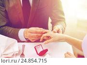 Купить «close up of man putting ring to his fiance finger», фото № 24854715, снято 9 марта 2014 г. (c) Syda Productions / Фотобанк Лори