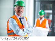 Купить «Architect in hard hat standing with blueprint in office corridor», фото № 24860851, снято 6 июля 2016 г. (c) Wavebreak Media / Фотобанк Лори