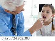 Купить «Doctor examining patient throat by using tongue depressor», фото № 24862383, снято 25 августа 2016 г. (c) Wavebreak Media / Фотобанк Лори