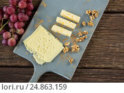 Купить «Pieces of cheese, walnut and grapes on chopping board», фото № 24863159, снято 16 сентября 2016 г. (c) Wavebreak Media / Фотобанк Лори