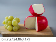 Купить «Gouda cheese with grapes on chopping board», фото № 24863179, снято 16 сентября 2016 г. (c) Wavebreak Media / Фотобанк Лори
