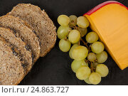 Купить «Slices of brown bread, grapes and gouda cheese on slate board», фото № 24863727, снято 16 сентября 2016 г. (c) Wavebreak Media / Фотобанк Лори