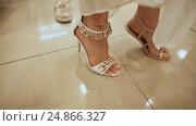 Купить «The girl tries on sandals foot in shoe store», видеоролик № 24866327, снято 7 января 2017 г. (c) Mikhail Davidovich / Фотобанк Лори