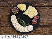 Купить «Slices of cheese, rosemary and nacho chips on plate», фото № 24867967, снято 16 сентября 2016 г. (c) Wavebreak Media / Фотобанк Лори