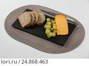 Купить «Brown bread, grapes and gouda cheese with knife on slate board», фото № 24868463, снято 16 сентября 2016 г. (c) Wavebreak Media / Фотобанк Лори