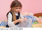 Купить «Грустная девочка сидит на кровати и лопает пузырьки на упаковочной пленке», фото № 24870283, снято 13 января 2017 г. (c) Иванов Алексей / Фотобанк Лори