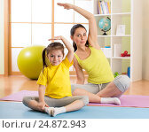 Купить «Portrait of kid and mother doing physical exercise at home», фото № 24872943, снято 14 декабря 2016 г. (c) Оксана Кузьмина / Фотобанк Лори