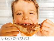 Купить «Happy kid boy eating toast with chocolate spread», фото № 24873763, снято 4 декабря 2016 г. (c) Сергей Новиков / Фотобанк Лори
