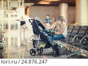 Купить «Mom and infant communicate while waiting for his flight at the airport on the chairs», фото № 24876247, снято 12 ноября 2019 г. (c) Mikhail Starodubov / Фотобанк Лори