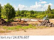 Купить «Бульдозер работает на строительной площадке с фундаментом нового загородного дома», фото № 24876607, снято 1 июля 2016 г. (c) FotograFF / Фотобанк Лори