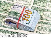 Купить «Сложенная пачка американских долларов, перетянутая резинкой, лежит на банкнотах», фото № 24885007, снято 29 февраля 2020 г. (c) FotograFF / Фотобанк Лори