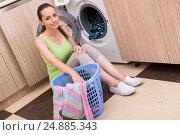 Young wife woman washing clothes near machine. Стоковое фото, фотограф Elnur / Фотобанк Лори