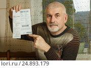 Пожилой мужчина показывает оплаченную квитанцию. Стоковое фото, фотограф Акиньшин Владимир / Фотобанк Лори
